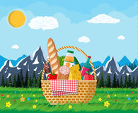 WIcker picnic basket full of products and nature. WIcker picnic basket full of products, wine, sausage, bacon and cheese, apple, tomato, cucumber, salad, juice Stock Photography