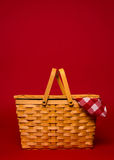 A wicker picnic basket with red gingham tablecloth on a red back. A brown, wicker picnic basket with red gingham tablecloth on a red background with copy space Royalty Free Stock Photo