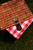 Wicker picnic basket with a red and white gingham cloth on grass. Wicker picnic basket with a red and white gingham cloth on a grass background Royalty Free Stock Photos