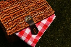 Wicker picnic basket with a red and white gingham cloth on grass. Wicker picnic basket with a red and white gingham cloth on a grass background Royalty Free Stock Photography
