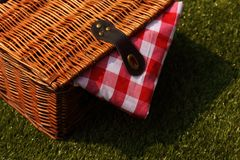 Wicker picnic basket with a red and white gingham cloth on grass. Wicker picnic basket with a red and white gingham cloth on a grass background Royalty Free Stock Photo