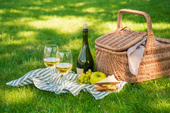 Wicker picnic basket, sandwich, fruits and bottle of wine with glasses on napkin Stock Photos