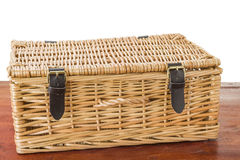 Wicker picnic basket sitting on mahogany wood table. Wicker picnic basket with leather brass buckled straps sitting on mahogany wood table. Isolated on white Stock Photo