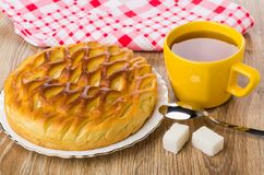 Pie with cottage cheese, cup of tea, sugar and teaspoon. Wicker pie with cottage cheese in plate, cup of tea, sugar and teaspoon on wooden table Royalty Free Stock Photos
