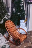 Wicker rattan chair, in a Christmas interior with a snowman. And Christmas trees Stock Image