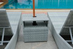 Wicker rattan pool sun bed deckchair at swimming pool. Wicker rattan pool sun bed deckchair at poolside of swimming pool. summer holiday vacation stock image