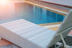 Wicker rattan pool sun bed deckchair at swimming pool. Wicker rattan pool sun bed deckchair at poolside of swimming pool. summer holiday vacation stock images