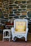 Wicker rocker on porch. Vertical photo of white wicker rocker and table on porch with stone wall in background Royalty Free Stock Photo