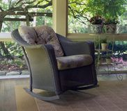 Wicker rocking chair. On screened porch for summer relaxation stock photo