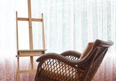Wicker rocking chair and wooden easel composition Stock Images