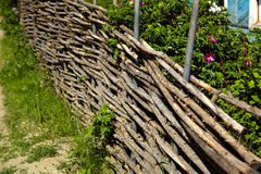 Wicker rustic fence in the garden Stock Images