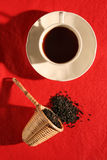 A wicker scoop with herb tea leaves and a cup of t Stock Photography
