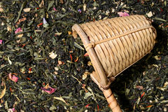 Wicker scoop over a tea leaves background Stock Photos