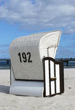 Wicker seat on sandy beach Stock Photography