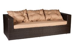 Wicker sofa with linen cushions in sand color. Wicker sofa with linen cushions in a sand color royalty free stock photos