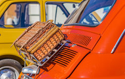 Wicker suitcase on luggage rack. Of ancient Italian subcompact red car Royalty Free Stock Images