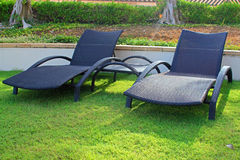 Wicker sun loungers. On the grass in the sun Stock Photo