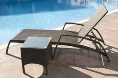 Wicker sunbed by the blue swimming pool. Luxury brown wicker rattan sunbed and coffe table by the blue swimming pool stock images