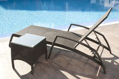 Wicker sunbed by the blue swimming pool. Luxury brown wicker rattan sunbed and coffe table by the blue swimming pool royalty free stock photo