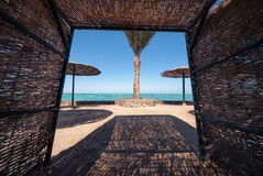 Wicker sunshade shelter hovel on the beach in ocean sea resort. Vacation summer time.  royalty free stock image