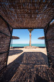 Wicker sunshade shelter hovel on the beach in ocean sea resort. Vacation summer time.  royalty free stock images