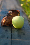 Wicker toy clog and yellow apple Royalty Free Stock Photo