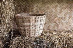 Wicker trash basket at rural house. Wicker trash basket on dry grass of traditional rural wooden house Stock Photography