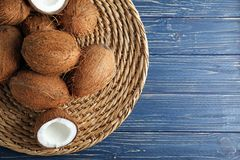 Wicker tray with coconuts. On wooden background Royalty Free Stock Photos