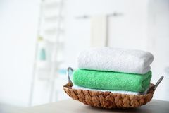 Wicker tray with towels on table. Against blurred background royalty free stock image