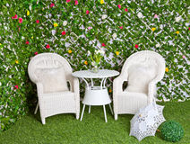 Wicker white furniture in the blooming garden. White wicker rattan furniture in the blooming garden. Vintage tracery umbrella royalty free stock images