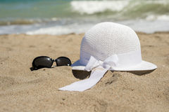 Wicker white hat and sunglasses on the beach Royalty Free Stock Photography