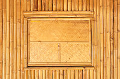 Wicker window panel on dry bamboo wall Stock Photo