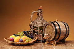 Wicker wine bottle, grapes and wooden barrel. On the table royalty free stock photos