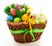 Wicker wooden basket with Easter eggs and fresh grass Stock Image