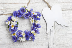 Wicker wreath decorated with cornflowers and chamomiles, and woo Royalty Free Stock Image