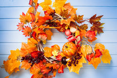 Wicker wreath decorated orange leaves, autumn vegetables Stock Images