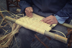 Wickerwork. Old man weaves a product Royalty Free Stock Photos