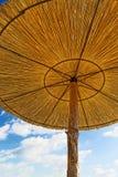 Wickerwork Sun Umbrellas on the beach Royalty Free Stock Photos