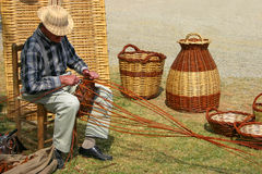Wickerworker. Craftsman working with wicker Stock Photography
