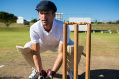 Wicket keeper crouching by stumps during match. On sunny day stock image