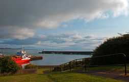 Wicklow Ireland North Harbor Commercial Dock with seawall jetty and Lighthouse in the background Royalty Free Stock Image