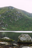 A Wicklow mountain next to a lake with some rocks. In the lake royalty free stock images