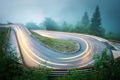 Wicklungsgebirgsstraße mit Autolichtern Nebeliges regnerisches Wetter und niedrige Sicht Alpen, Slowenien stockfotografie
