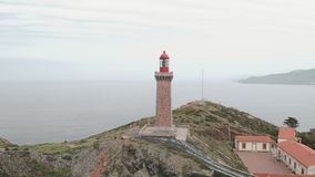 Wide aerial shot of lighthouse on the coast above the ocean in Catalonia, Spain stock footage