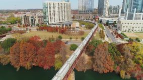 Wide aerial view of cargo train and Austin city skyline. A wide rising aerial establishing shot of a cargo train traveling over a railroad bridge over the stock video