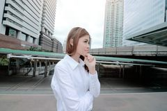 Wide angel shot of confident young Asian woman standing and thinking posing at urban building public background. Wide angel shot of confident young Asian woman Stock Photos