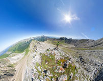 Wide-angle aerial panorama A man stands on top in the mountains Royalty Free Stock Photography