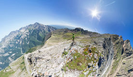 Wide-angle aerial panorama A man stands on top in the mountains Stock Images