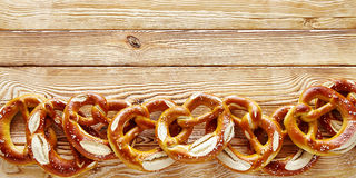 Wide angle border of Bavarian pretzels on wood Stock Image