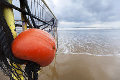 Winter Beach Buoy and Fence. Wide angle close-up of an old red buoy hanging from a corroded fence from a black sand covered rock, located at the beach on an Stock Photos